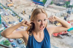 A young woman by the window annoyed by the building works outside. Noise concept.  royalty free stock photo