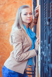 Young woman by the window with forged bars. Woman standing near the window. on the window forged metal lattice Stock Images