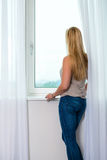 Young woman at window in hotel room Royalty Free Stock Photography