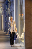 Young woman window shopping evening city Stock Photo