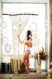 A young woman on the window weaves macrame curtains. Macrame hobby weaving dream catchers, feathers. Girl weaves threads stock image