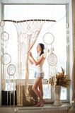 A young woman on the window weaves macrame curtains. Macrame hobby weaving dream catchers, feathers. Girl weaves threads royalty free stock images