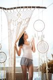 A young woman on the window weaves macrame curtains. Macrame hobby weaving dream catchers, feathers. Girl weaves threads stock images