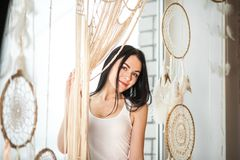 A young woman on the window weaves macrame curtains. Macrame hobby weaving dream catchers, feathers. Girl weaves threads royalty free stock image