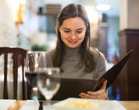Young woman with wine looking at menu Stock Image