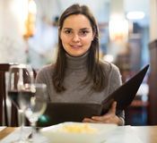 Young woman with wine looking at menu Stock Photos
