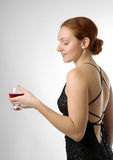 Young woman with wineglass, half-turn. Adult girl in black cocktail dress with back naked, glass of wine in left hand, gaze lowered, long red hair arranged nape Royalty Free Stock Photo