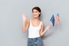 Young woman winking and holding flags Royalty Free Stock Image