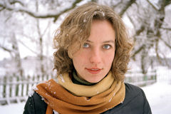 Young woman in Winter. Portrait of young woman in scarf with snowy Winter background Royalty Free Stock Images