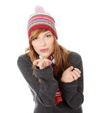 Young woman with winter cap. Close up of young woman with winter cap sending a kiss to the camera isoalted on white background Royalty Free Stock Image