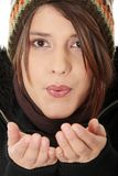 Young woman with winter cap. Close up of young woman with winter cap sending a kiss to the camera isoalted on white background Stock Images