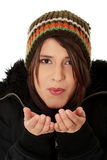Young woman with winter cap. Close up of young woman with winter cap sending a kiss to the camera isoalted on white background Stock Photography