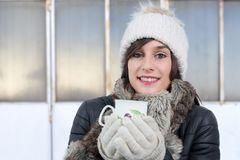 Young woman with winter cap drinking cup of tea Royalty Free Stock Photos