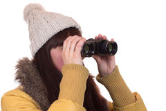 Young woman with a winter cap looking through binoculars Royalty Free Stock Photo