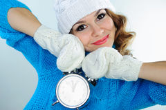 Young woman in winter clothes holding alarm clock Stock Photography