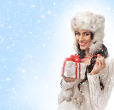 A young woman in winter clothes holding a present Stock Images