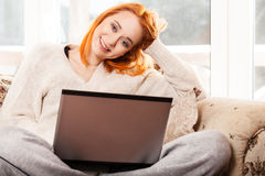 Young woman in winter clothes with laptop Royalty Free Stock Image