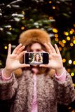 Young woman in winter clothes making selfie using a smart phone and smiling on christmas lights background royalty free stock photos