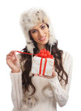 A young woman in winter clothes opening a present Stock Photography