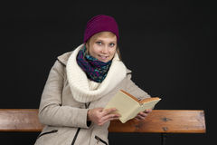 Young woman in winter clothes reading on a bench Royalty Free Stock Photography