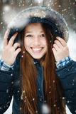 Young woman in winter clothes standing under the snow Stock Photos