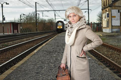 Young woman in winter clothes waiting for her train Royalty Free Stock Images