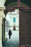 Young woman in winter clothes walks her dog inside Strahov Monastery Stock Image