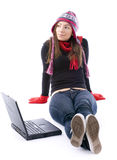 Young woman in winter clothes working on laptop Royalty Free Stock Photography