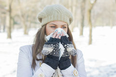 Young Woman in Winter Clothing Blowing Nose Stock Photography