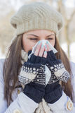 Young Woman in Winter Clothing Blowing Nose Royalty Free Stock Photography