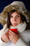 Young woman in winter coat drinking hot coffee Royalty Free Stock Photos