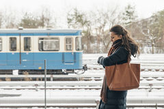 Young woman in winter coat looking her watch waiting for train. Stock Image