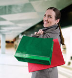Shoping. Young woman in winter coat purchases in bags Royalty Free Stock Images