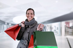 Shoping. Young woman in winter coat purchases in bags Stock Photos