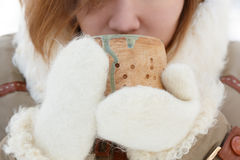 Young woman in winter coat and white fluffy mittens holds potter Royalty Free Stock Image