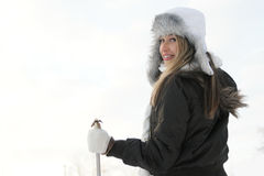 A young woman in a winter dress holding ski sticks Royalty Free Stock Photo