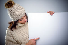 Young woman in winter fashion pointing to a sign Stock Photography