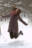 Young woman in the winter forest. Young woman is jumping over snow in the winter forest Royalty Free Stock Image