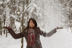 Young woman in the winter forest. Young woman is playing with falling snow in the winter forest Royalty Free Stock Photos