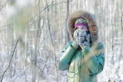 Young woman in winter frost forest hiding her face in woolly scarf and mittens outdoors. Young woman in winter frost forest is hiding her face in woolly scarf Royalty Free Stock Photos