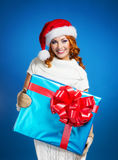 A young woman in a winter hat holding a present Stock Photos