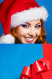 A young woman in a winter hat holding a present Royalty Free Stock Images