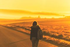 Young woman in the winter jacket with a backpack on the road against the background of the sunrise autumn field. royalty free stock photos