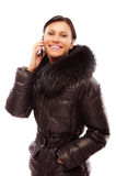 Young woman in a winter jacket speaks on phone Stock Image