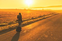 Young woman in the winter jacket with suitcase on the road against the background of the sunrise autumn field. stock images