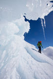 Young woman in winter mountains. Alpinist descending snow covered mountain slope Stock Photo