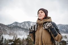 Young woman in the winter mountais. Backpacker girl listening the music in the mountains in winter stock photo
