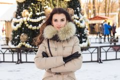 Young woman in winter park near christmas tree Royalty Free Stock Photo