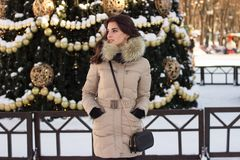 Young woman in winter park near christmas tree Royalty Free Stock Photos