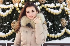 Young woman in winter park near christmas tree Stock Photos